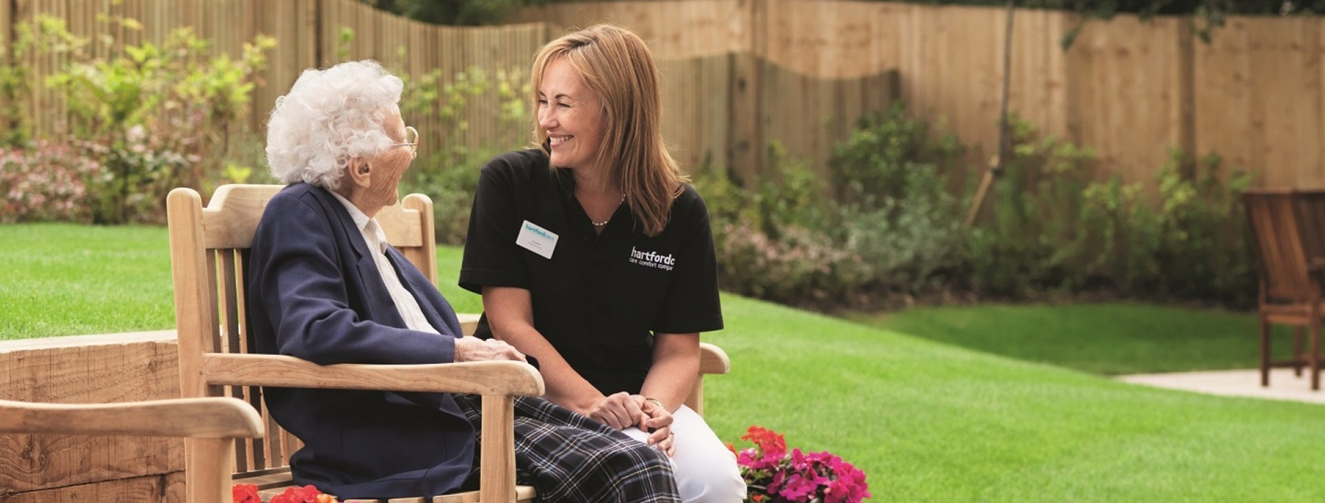 Care assistant and patient chatting on a bench